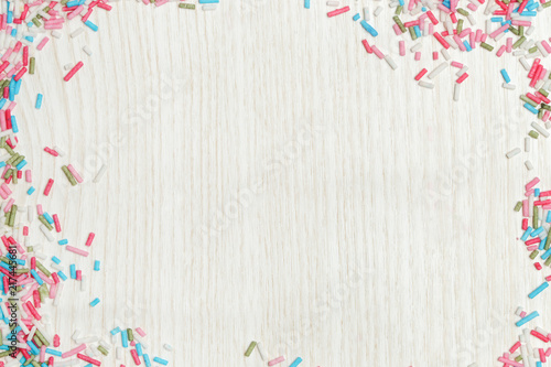 Photo  Colorful sprinkles around wooden background, party design element