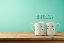Coffee Cups With Funny Faces On Wooden Table