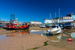 Colorful fishing and pleasure boats aground on the sand in Tenby harbour at low tide