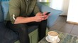 young athletic man, takes a picture of a cup with a coffee drink on a smartphone, resting sitting at a table in a cafe. communication in social networks, on the Internet