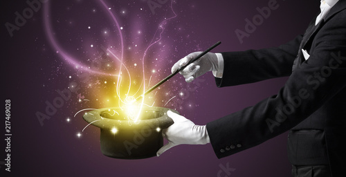 Foto Magician hand conjure with wand  light from a black cylinder