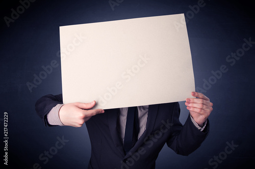 Fotografie, Obraz  Young businessman hiding behind a blank piece of paper