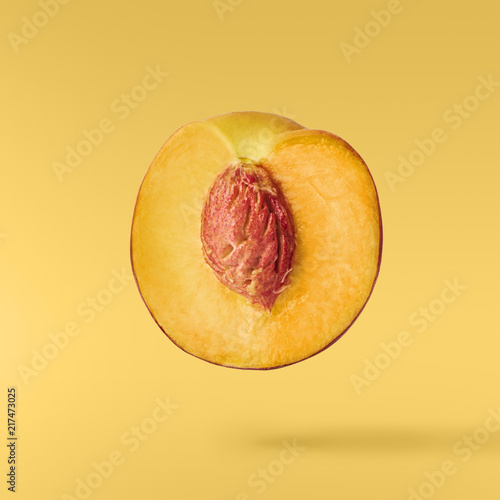 Fotografia Flying fresh ripe peach with green leaves isolated