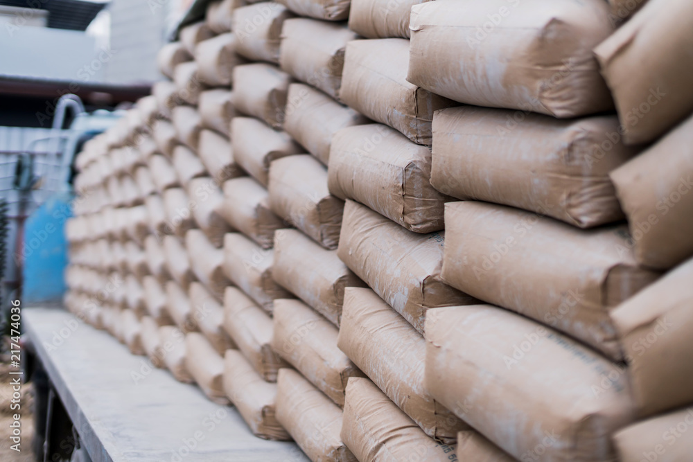 Fototapeta row of raw cement bag stack on truck site construction ideas concept