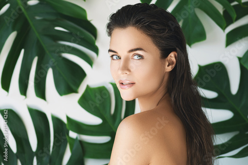 Obraz na plátně  Portrait of young and beautiful woman with perfect smooth skin in tropical leave