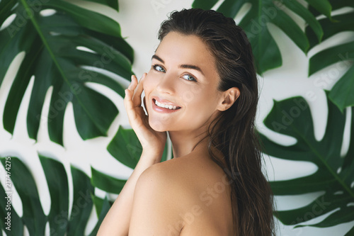 Portrait of young and beautiful woman with perfect smooth skin in tropical leave Fotobehang