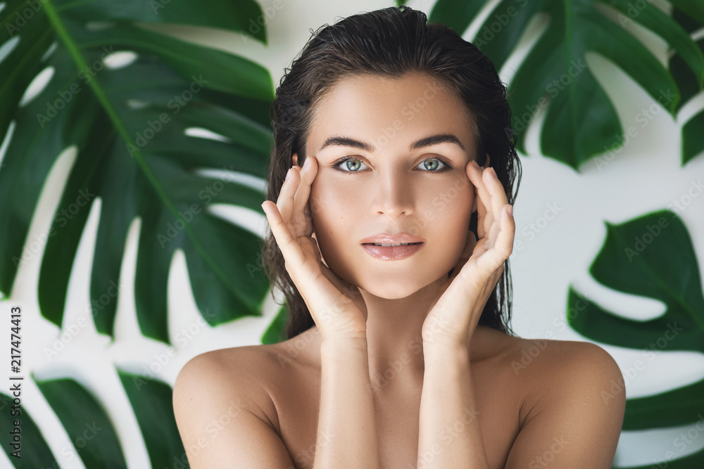 Fototapeta Portrait of young and beautiful woman with perfect smooth skin in tropical leaves