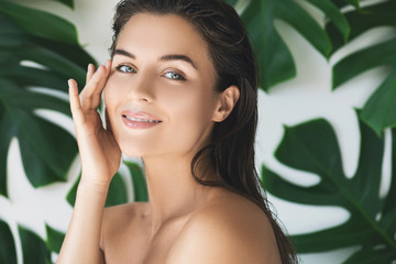 Fototapeta Do Spa Portrait of young and beautiful woman with perfect smooth skin in tropical leaves