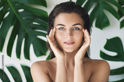 Obraz Portrait of young and beautiful woman with perfect smooth skin in tropical leaves - fototapety do salonu