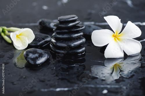 czarne-kamienie-do-masazu-z-bialymi-kwiatami-w-wodzie