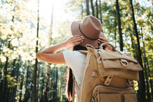 Young Hipster Woman Traveling Alone On Outdoors Among Trees And Hold Hat His Hands. Handsome Girl Wearing Traveler Backpack