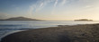 Angel Island and Alcatraz silhouetted against early morning sky. Wet sand and bay water foreground. Light clouds.