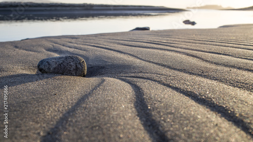 Photo  Textured beach sand foreground with small rock, tidal stream and Alcatraz Island behind