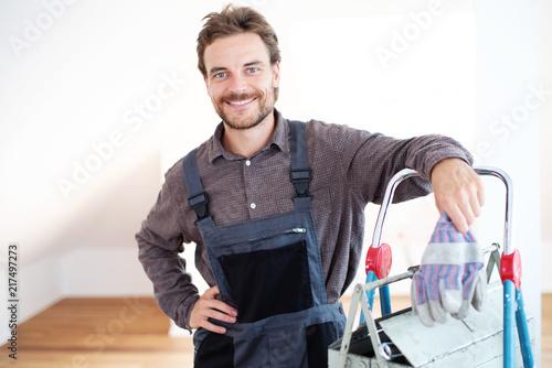 Fotomural Handwerker sympathisch lächelnd in einem Gebäude