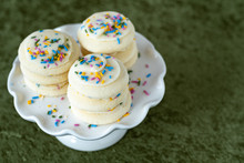 Three Stacks Of Vanilla Frosted Sugar Cookies With Multi-color Sprinkles On A White Cake Plate, On A Green Background