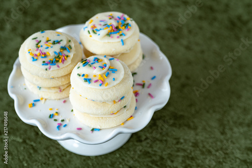 Canvas Print Three stacks of vanilla frosted sugar cookies with multi-color sprinkles on a wh