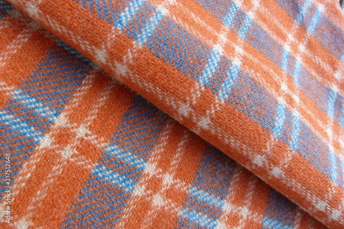 Fotobehang Stof woolen fabric in a cage close-up gray orange stripes squares drape nap vintage coat plaid background for decor rolls cloth folds on fabric natural material