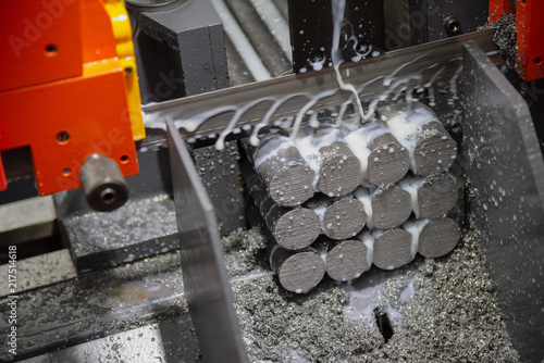 Fotografía  The  band saw machine cutting raw metals rods the  with the coolant fluid