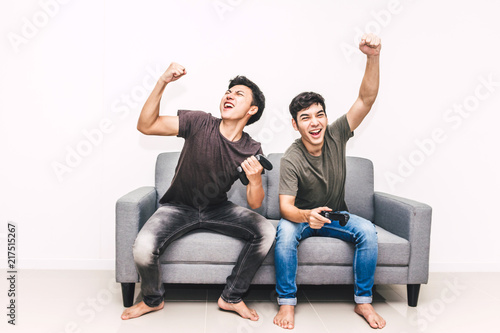 Two friends sitting on sofa and enjoying play video game together at home Fototapeta