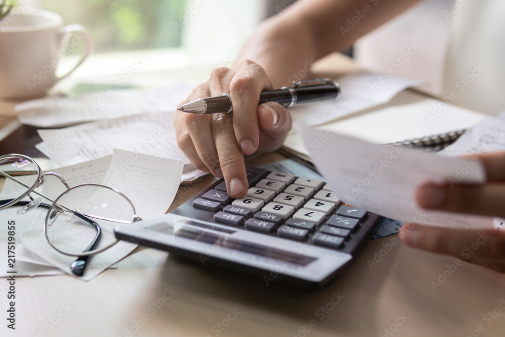 Fototapeta Stressed young woman checking bills, taxes, bank account balance and calculating expenses in the living room at home