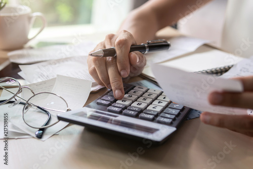 Valokuva  Stressed young woman checking bills, taxes, bank account balance and calculating