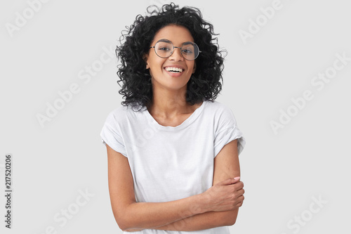 Fotografía  Joyful African American student keeps hands crossed, laughs at good joke, wears casual clothes and round spectacles, isolated over white background