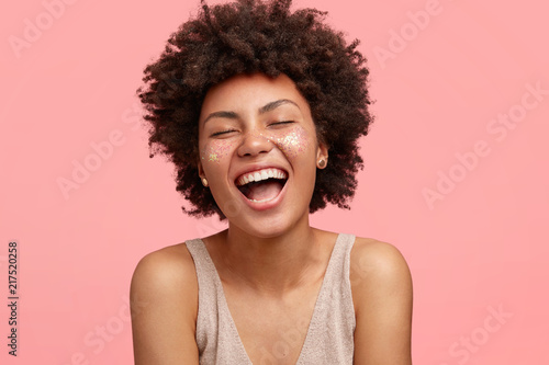 Fototapeta Joyful African American female with dark skin, laughs happily, opens mouth widely, has sparkles on cheeks, closes eyes, has curly hair, isolated over pink background