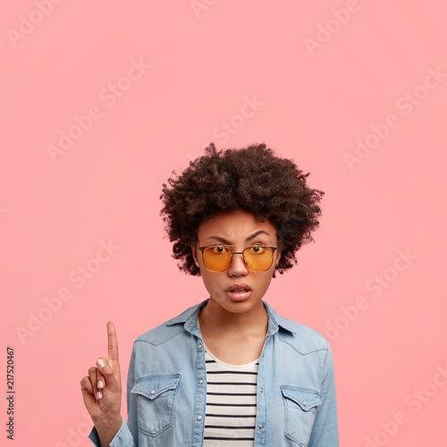 Fotografie, Obraz  Fashionable serious annoyed beautiful African American female in trendy yellow shades and denim jacket, points with index finger upwards, shows free space above, expresses negative emotions