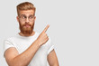 Horizontal shot of attractive Caucasian male has ginger hair and beard, points with fore finger aside, dressed in t shirt in one colour with background, shows blank space for your advertisement