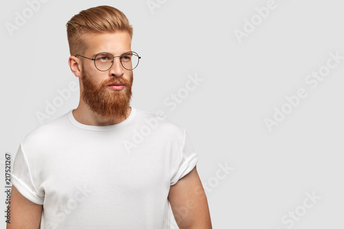 Brutal young handsome man with ginger beard, trendy hairstyle, wears casual white t shirt and spectacles, looks aside, stands against white background with free space for your advertisement.