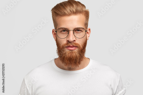 Fotografia Headshot of attractive serious Caucasian male with thick ginger beard and trendy