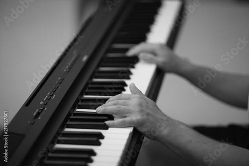 Photo Hands of the musical accompanist on the keys of the digital electric piano