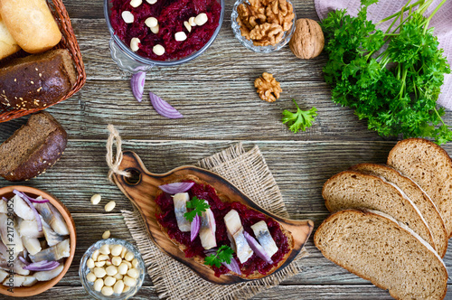 Fotografía  Boiled grated beets, pieces of herring, red onions, nuts on whole grain bread