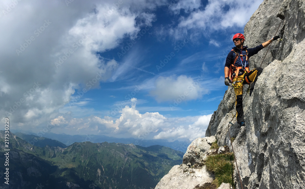 Fototapety, obrazy: Young man climbing on a rock in Swiss Alps - via ferrata/klettersteig