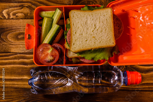 Foto op Aluminium Assortiment Bottle of water and lunch box with sandwich, cucumbers and tomatoes on wooden table. Top view