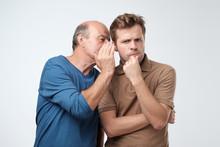 Senior Man Sharing Secret Or Whispering Gossips Into His Son Ear. Telling Family Secret Concept