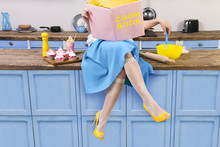 Colorful Retro / Pin Up Girl Woman Female Housewife Wearing Yellow Top, Skirt And White Apron Sitting On Kitchen And Reading Pink Cook Book. Sweet Food Cupcakes And Milkshake Home Cooked On The Table