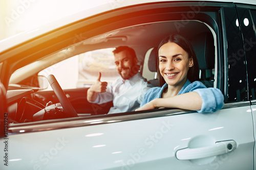Fotografie, Obraz  Happy smiling young couple chooses and buying a new car for the family in the dealership in sunlight