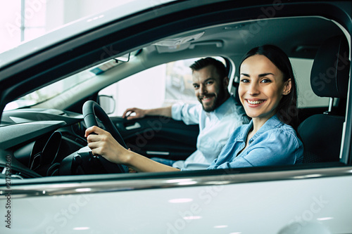 Fotografie, Obraz  Happy beautiful young couple chooses and buying a new car for the family in the dealership while sitting inside one of car