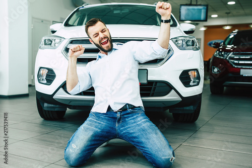 Fototapeta Happy handsome man buying a new white car in dealership and dancing on the floor against the auto. obraz