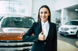 Portrait of beautiful young saleswoman in black suit standing inside dealership while shows thumbs up