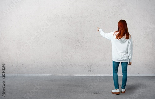 Obraz Young redhead girl in an urban white sweatshirt with glasses pointing back with the index finger presenting a product from behind and standing on a vintage gray wall - fototapety do salonu