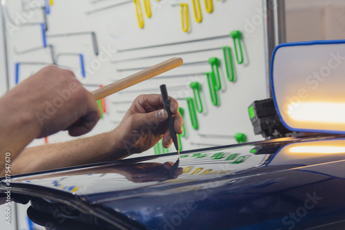 Fotografie, Obraz  Hands of the worker working on straightening the car. Car service