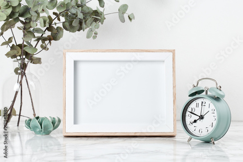 Fototapeta Poster frame mockup, front view, with decor elements, flowers and blank copy space over the white wall. obraz
