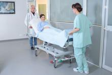 Nurses Moving Patient Through Hospital Hallway