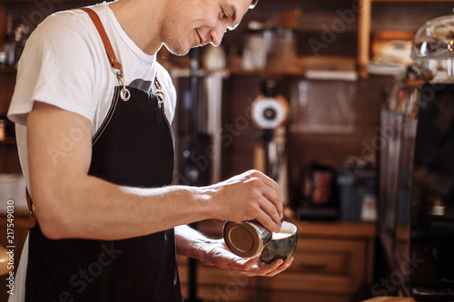 Fotografie, Obraz  cheerful barista man preparing beverage from coffee at the cafe