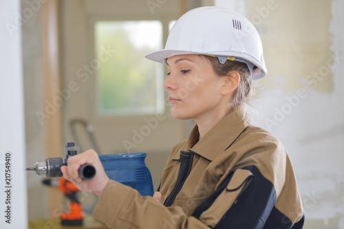Fotografie, Obraz  female builder drills hole in the wall