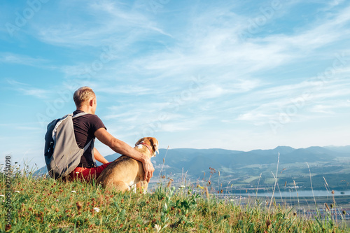 Man with his beagle dog sits on the top of hill over the mountain valley фототапет