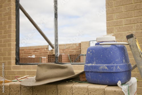A water bottle and hat on a residential building site.