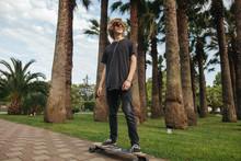 Young Boy Riding Longboard On Boardwalk, Warm Summer Time